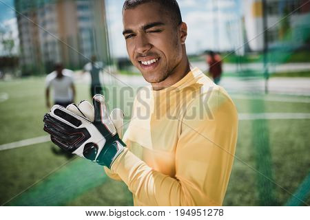 portrait of african american goalkeeper in soccer gloves on pitch