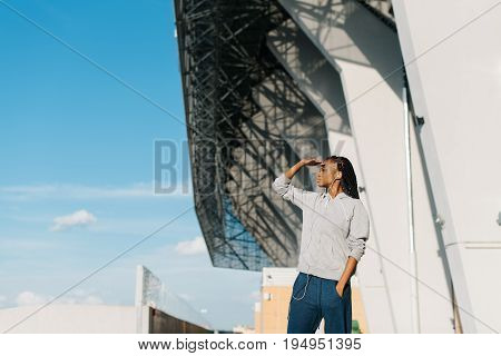 Side view of the concentated afro-american teenager holding the hand near the forehead and looking afar at the background of the blue sky