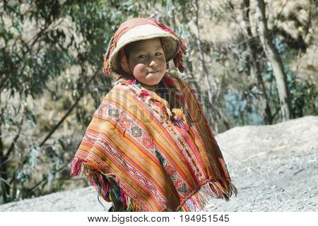 Smiling native peruvian boy wearing colorful handmade traditional poncho and a hat. October 21 2012 - Patacancha, Cusco, Peru