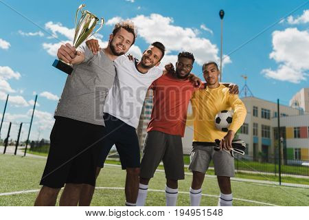 Multiethnic Soccer Team With Goblet Standing On Soccer Pitch After Game