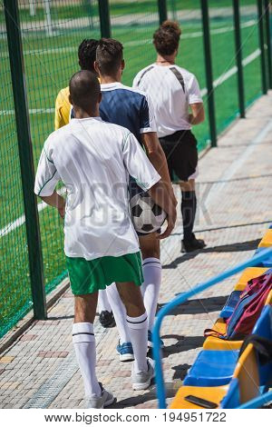 Back View Of Soccer Players And Referee Going On Soccer Pitch