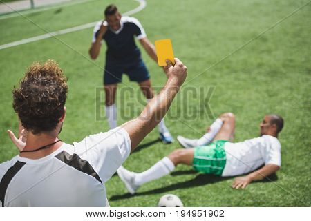 Back View Of Soccer Referee Showing Yellow Card To Players During Game