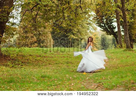 Bride Whirls Her Dress While Standing On The Green Hill