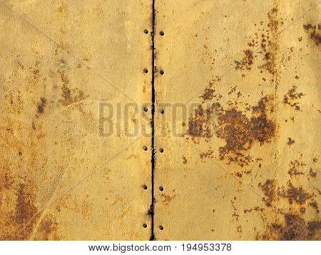 Two old metal sheets with a rust texture are connected together by bolts