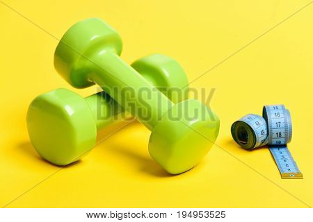 Blue Flexible Ruler With Green Dumbbells Isolated On Yellow