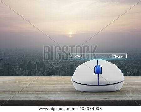 Search www button with wireless computer mouse on wooden table over modern city tower at sunset vintage style Searching system and internet concept