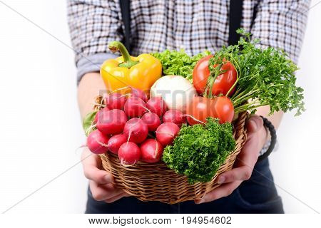 Farmers hands with harvest isolated on white background defocused. Idea of proper nutrition. Man holds basket full of fresh vegetables close up. Healthy lifestyle and diet concept
