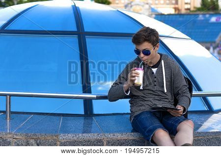 Young man with a tablet near a blue glass dome on a city street