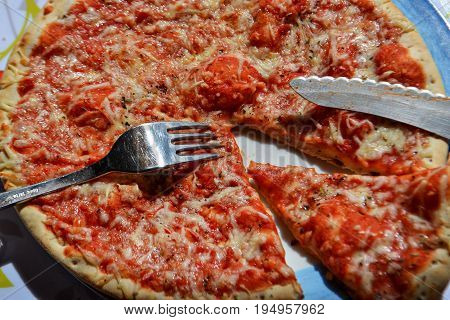 Pizza on a plate whit silver fork and knife