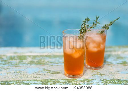 Alcohol orange cocktail on turquoise background. Close Up