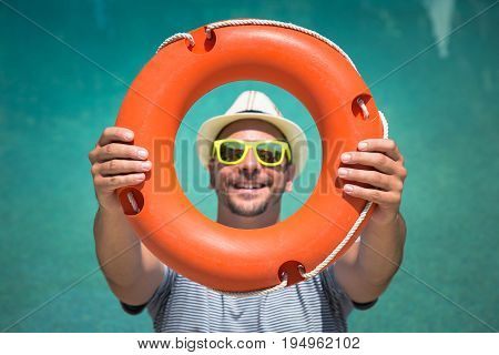 Portrait of young man showing and looking through lifebuoy outdoors. Tourism and summer vacation concepts.