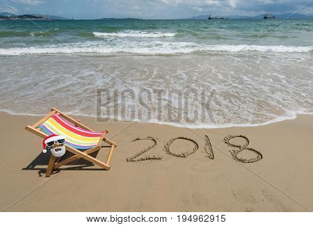 2018 written in sand write on tropical beach.Deck chair with Santa Claus sunglasses