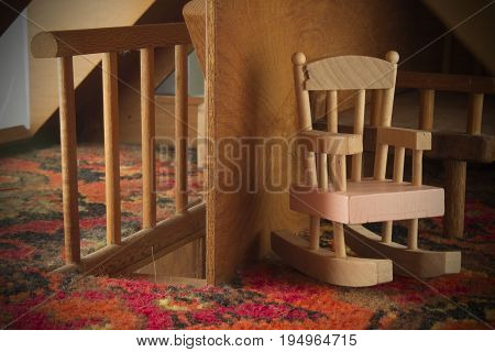 Pink wooden rocking chair next to staircase railing inside a dollhouse.