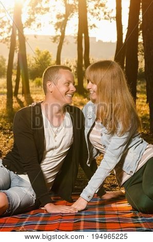happiness of the couple sitting on a bedspread in the woods in the sunset looking at each other