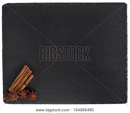 Cinnamon and star anise on a black slate board. Isolated on white background. Top view.