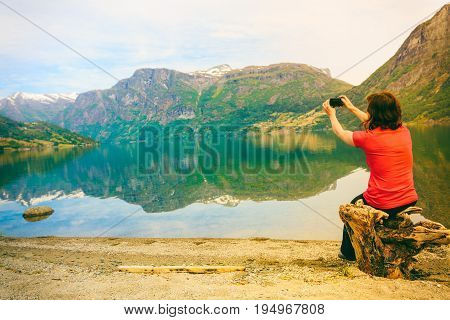 Tourism and travel. Woman tourist taking photo with camera enjoying mountains lake Oppstrynsvatnet view in Jostedalsbreen National Park Oppstryn (Stryn) Sogn og Fjordane county. Norway Scandinavia. poster