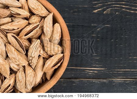 Part of bowl filled with unshelled almonds on wooden background