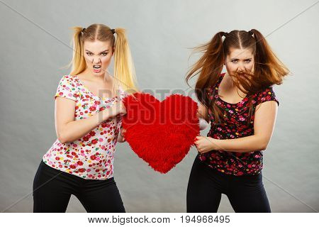 Two agressive young teenage women having argue fighting pulling heart shaped pillow. Female violance concept.