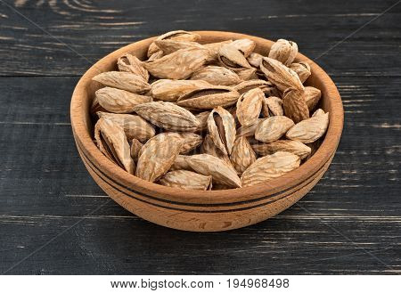 Uzbek inshell almonds in a bowl on wooden background