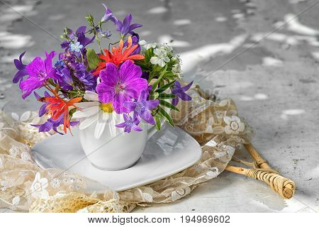 wild flowers bouquet with blue bells chamomiles and forget me not in a white tea cup with copy space