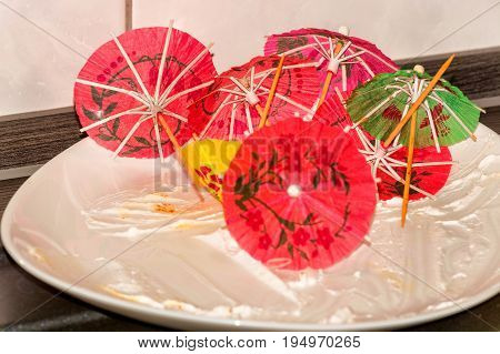 Empty white cake plate plate on a kitchen plate with colorful paper decoration umbrella.