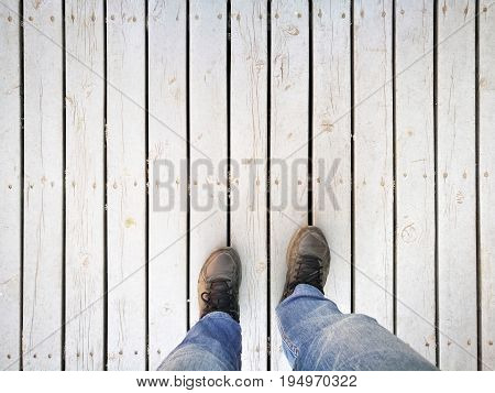 Human feet and legs seen from above; standing on dirty white wooden pathway; wearing dusty sport shoes and blue jeans in backpacker style  - Top copyspace