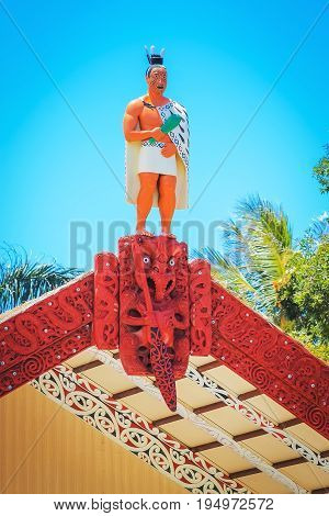 Honolulu Hawaii - May 27 2016: A carved wooden statue of a Maori man on top of the meeting house on the Marae at the Aotearoa Village inside the Polynesian Cultural Center on Oahu.