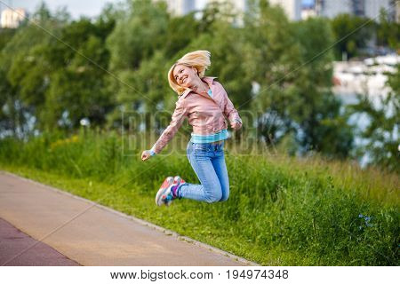Portrait of woman jumps and smilling in park