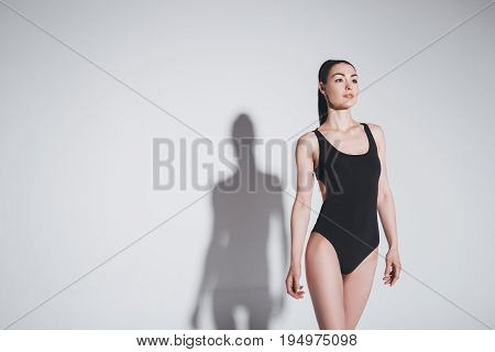 Beautiful Brunette Woman In Black Stylish Bodysuit Smiling And Looking Away In Studio