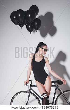 Stylish Young Woman In Black Bodysuit And Sunglasses Posing With Bicycle And Balloons In Studio