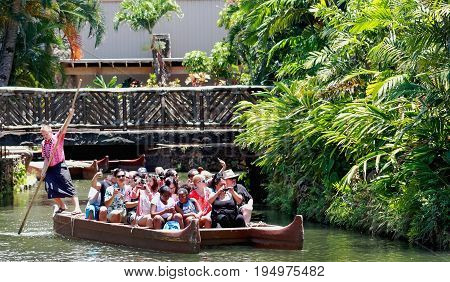 Honolulu Hawaii - May 27 2016:Visitors to the Polynesian Cultural Center a popular tourist destination are paddled down stream on a canoe by their tour guide.