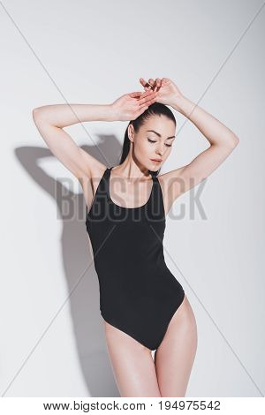Gorgeous Young Brunette Woman In Stylish Bodysuit Posing With Raised Hands On Grey