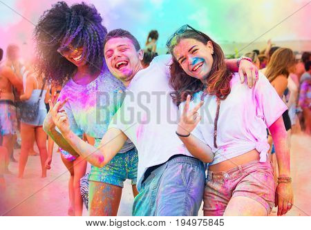 fun at holi party. young friends colored with color powder gulal laughing and enjoying the spring festival of colors.