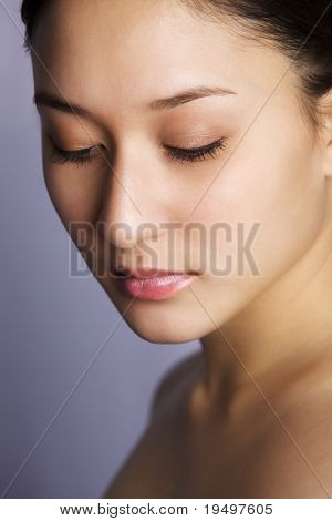 Beautiful asian-caucasian mix young woman on purple background looking down, looking straight