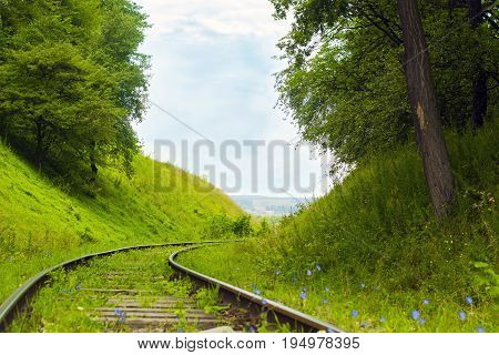 Old abandoned railroad among forested hills. Railway on country road. Rails among trees