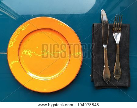 Orange glossy plate with cutlery on a dark napkin. The silver knife and fork lie on a black napkin. The plate stands on a blue glossy surface. Shooting from the top.