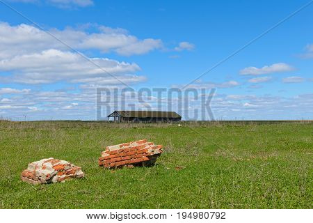 A green field with remains of a brick wall and a collapsing building on the horizon