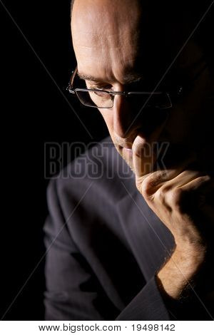Close-up of pondering businessman in suit looking down and supporting head on hand, low-key image.
