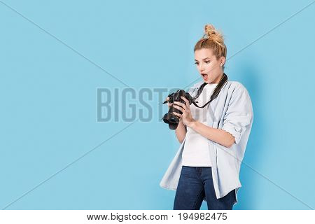 Young Blonde Photographer Is Shocked About Photo She Made. Model Isolated On A Blue Background With