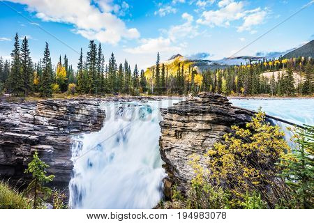 The full-water bubbling waterfall of Athabasca. Cold blue water at sunset. Clear autumn evening in Jasper National Park. The concept of extreme and ecological tourism