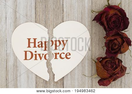 Happy divorce message Dead red roses with torn heart-shape card on weathered wood background with text Happy Divorve