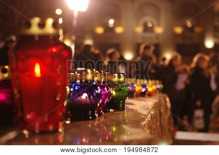 Colored candle lanterns on a stone pedestal