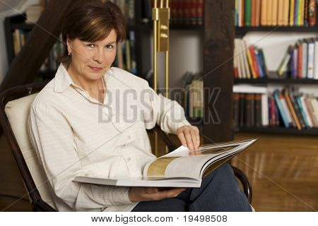 Sweet senior woman sitting in chair at home in front of bookshelves reading a book.