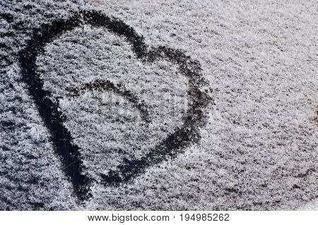 A drawing in the form of a heart on the fallen snow on the car glass