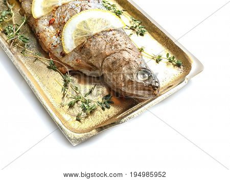 Golden tray with tasty fried fish on white background