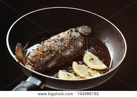 Frying pan with tasty trout fish and lemon slices, closeup