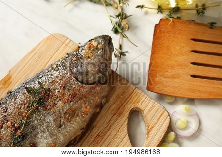 Tasty fried trout fish on wooden board