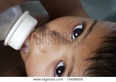 Sweet Indian baby with big eyes lying in parent's arms and being fed with baby bottle.
