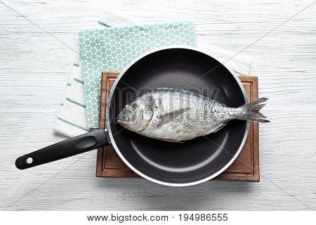 Frying pan with fresh dorado fish on table