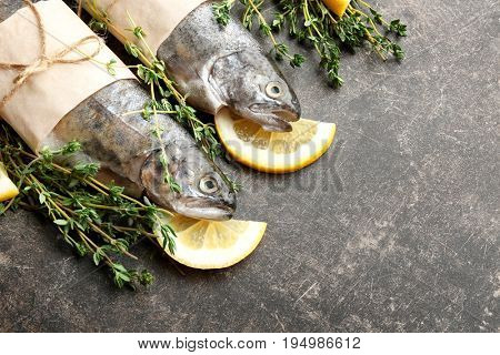 Composition with fresh trout fish wrapped in paper on gray background